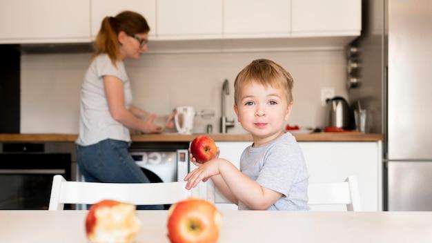 自宅で料理の小さな男の子の正面図 無料写真