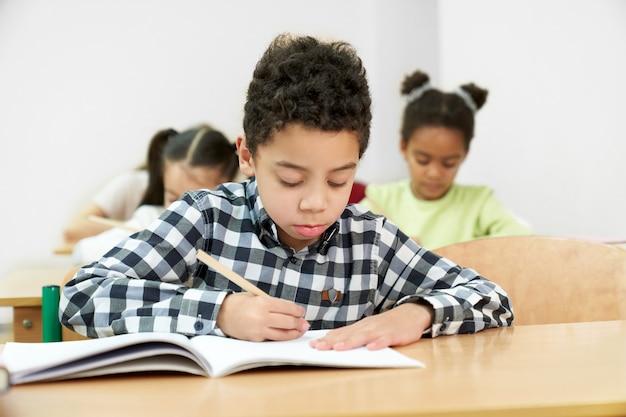 学校でテストを行っている途中の小さな男の子の正面図 Premium写真