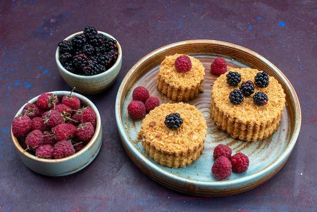 暗い表面に新鮮なベリーと甘くておいしい小さなケーキの正面図 無料写真
