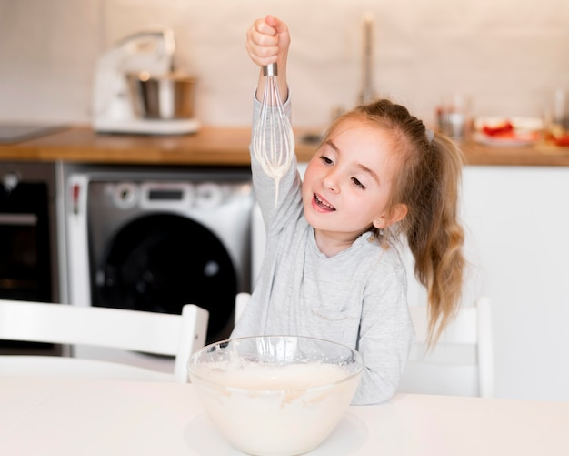 自宅で料理の小さな女の子の正面図 無料写真