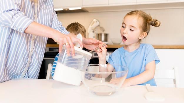 Вид спереди маленькой девочки, приготовление пищи дома Бесплатные Фотографии