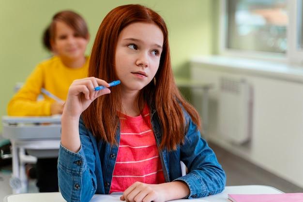 Вид спереди маленькой девочки в классе в школе Бесплатные Фотографии