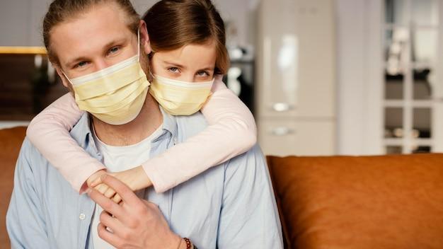 医療マスクを着用しながら父親と一緒に時間を過ごす少女の正面図 無料写真