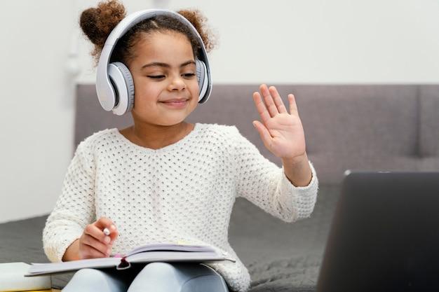 온라인 학교에 노트북을 흔들며 사용하는 어린 소녀의 전면보기 무료 사진