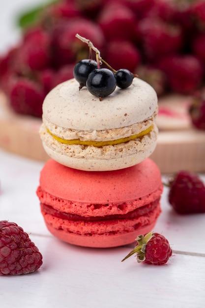 Вид спереди macarons с малиной на белой поверхности Бесплатные Фотографии