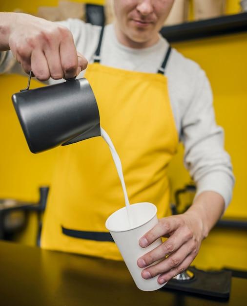 Вид спереди мужской бариста лить молоко в чашку Бесплатные Фотографии