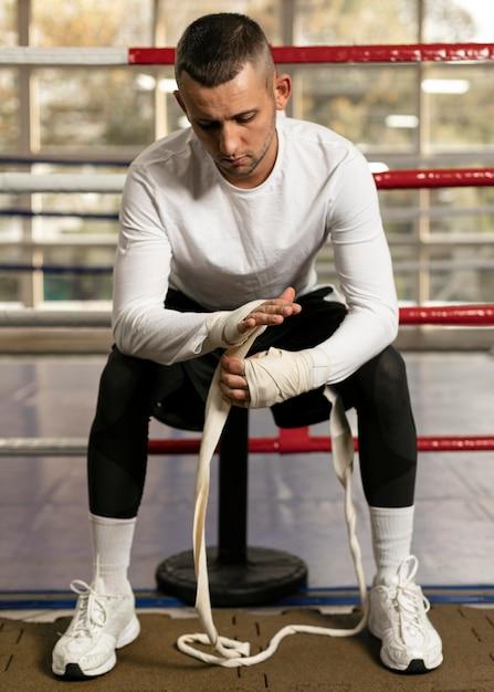 リングでトレーニングする前に手を包む男性ボクサーの正面図 無料写真