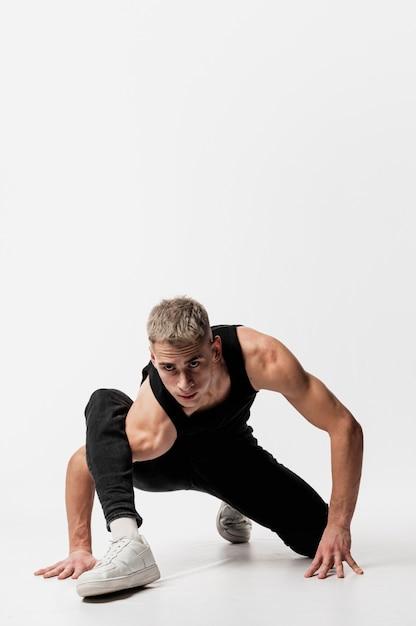 Вид спереди танцора в джинсах и майке позирует с копией пространства Бесплатные Фотографии