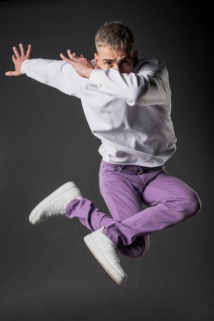 Вид спереди танцор в фиолетовых джинсах и кроссовках позирует в воздухе Бесплатные Фотографии