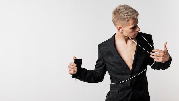 コピースペースとヘッドフォンで音楽を聴く男性ダンサーの正面図 無料写真