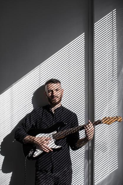 ウィンドウの横にあるエレクトリックギターを演奏する男性パフォーマーの正面図 無料写真