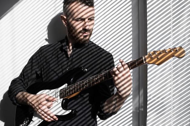 窓のブラインドの影でエレクトリックギターを演奏する男性パフォーマーの正面図 無料写真
