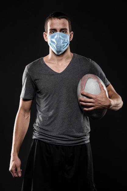 Вид спереди игрока в регби, держащего мяч в медицинской маске Бесплатные Фотографии