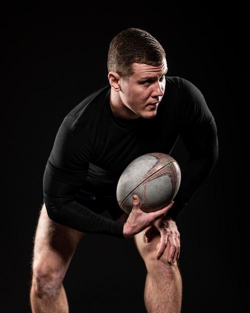 Вид спереди игрока в регби, держащего мяч одной рукой Бесплатные Фотографии