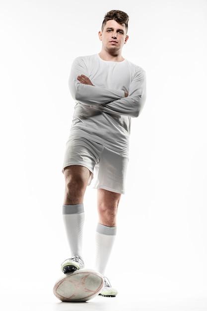 Вид спереди игрока в регби, позирующего со скрещенными руками и мячом Бесплатные Фотографии