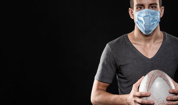 Вид спереди игрока в регби с медицинской маской и копией пространства Бесплатные Фотографии