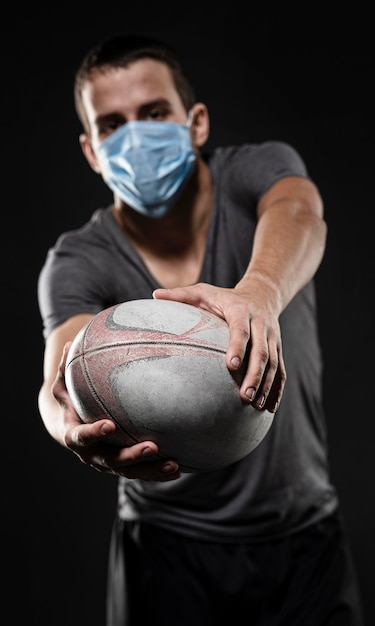 Вид спереди игрока в регби с медицинской маской, держащего мяч Бесплатные Фотографии