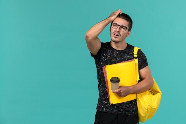 Вид спереди студента в темной футболке с желтым рюкзаком, держащего разные файлы и кофе, думающего на синей стене Бесплатные Фотографии