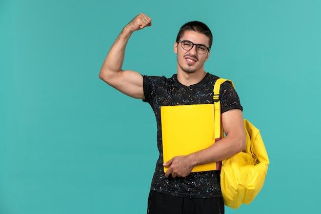밝은 파란색 벽에 구부리는 다른 파일을 들고 어두운 티셔츠 노란색 배낭에 남성 학생의 전면보기 무료 사진
