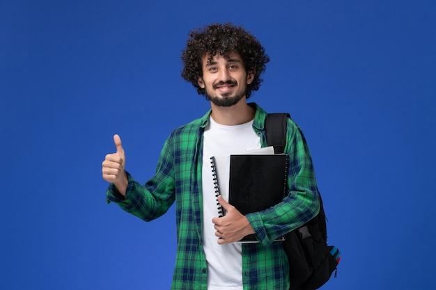 Вид спереди студента в зеленой клетчатой рубашке с черным рюкзаком, держащего тетради, улыбающегося на синей стене Бесплатные Фотографии