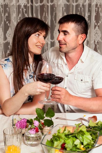 Вид спереди мужчины и женщины за обеденным столом с вином Бесплатные Фотографии
