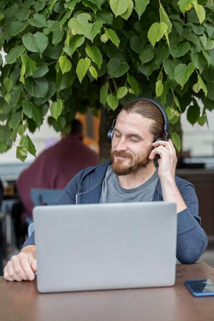 ノートパソコンとヘッドフォンで音楽を聴くテラスで男の正面図 無料写真