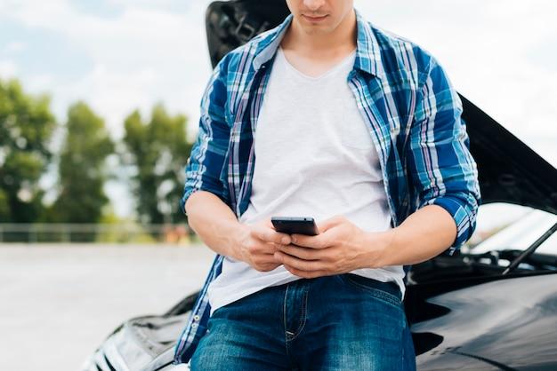 彼の携帯電話をチェックする男の正面図 無料写真