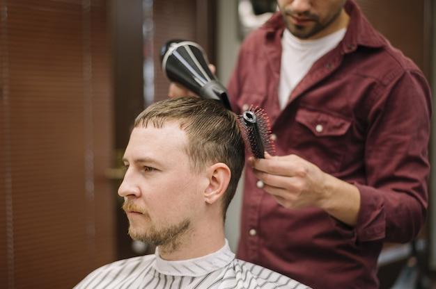 Вид спереди человека сушат волосы Premium Фотографии