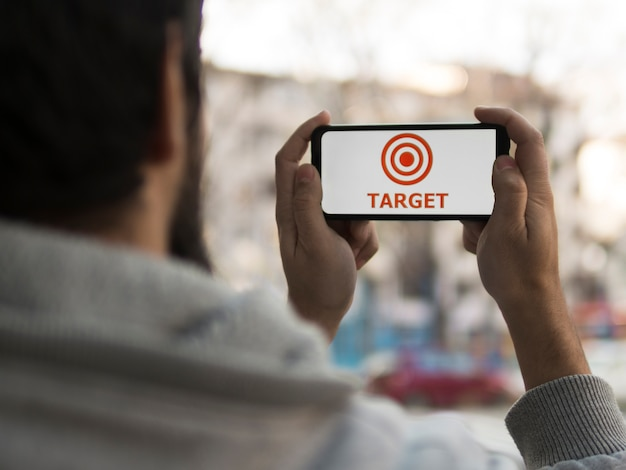 Вид спереди человека, подняв смартфон с целью Premium Фотографии