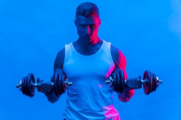 Вид спереди человека в майке, тренирующегося с весами Бесплатные Фотографии