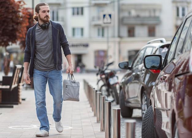Вид спереди человека в городе с сумкой для ноутбука Бесплатные Фотографии