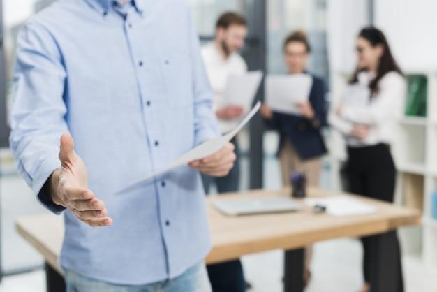Вид спереди человека в офисе, предлагая дрожание рук Бесплатные Фотографии