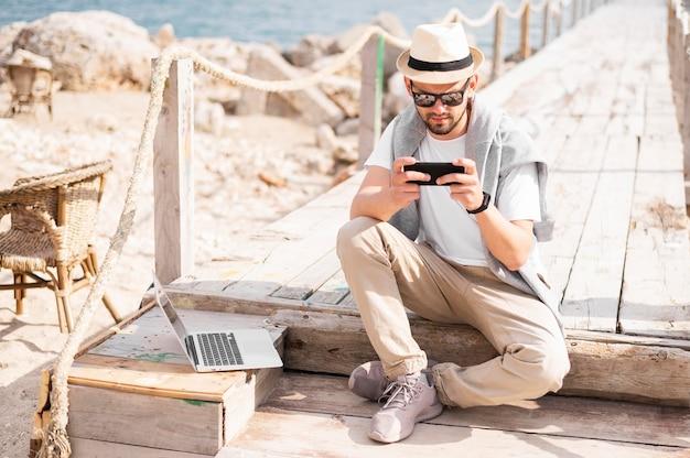 노트북과 스마트 폰에서 작업하는 해변 부두에 남자의 전면보기 무료 사진