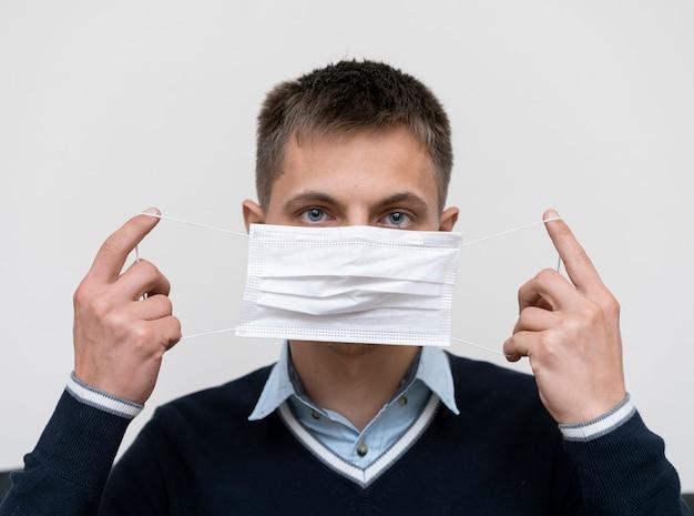 Вид спереди человека, надевающего медицинскую маску Бесплатные Фотографии