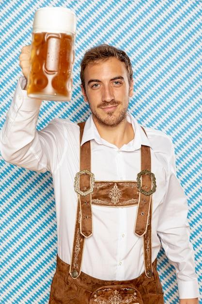 ビールパイントを上げる男の正面図 無料写真