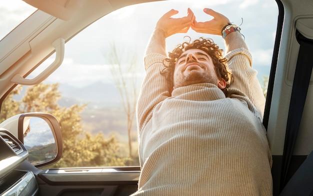 ロードトリップ中に車の中でストレッチする男の正面図 無料写真