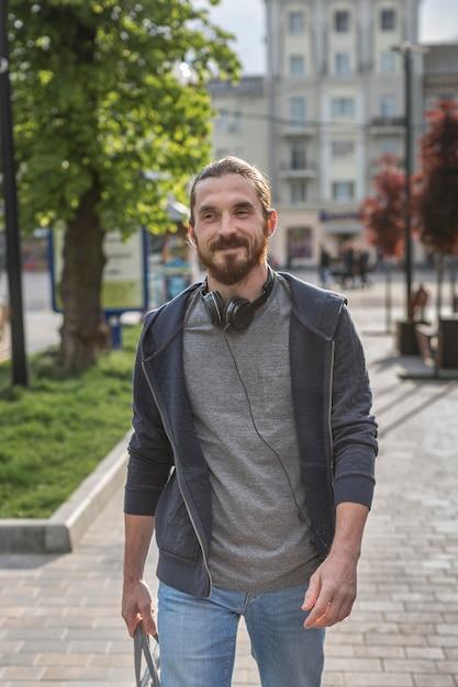 Вид спереди человека с наушниками в городе Бесплатные Фотографии