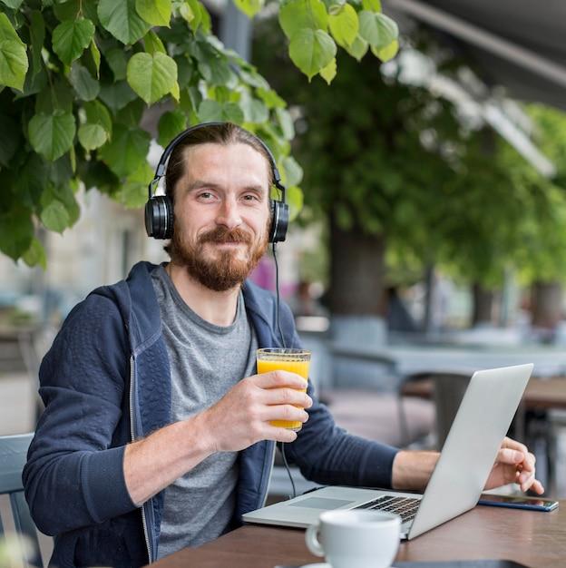 Вид спереди человека с соком на террасе с наушниками и ноутбуком Бесплатные Фотографии