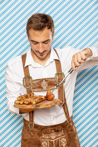 ドイツのソーセージのプレートを持つ男の正面図 無料写真