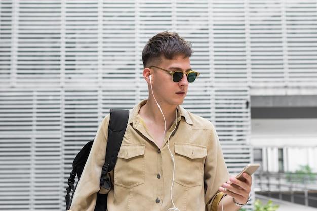 Вид спереди человека в солнцезащитных очках, слушающего музыку в наушниках Бесплатные Фотографии