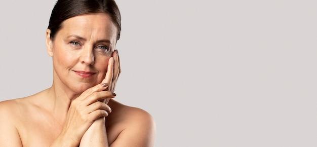 Вид спереди зрелой женщины, позирующей с макияжем и копией пространства Бесплатные Фотографии