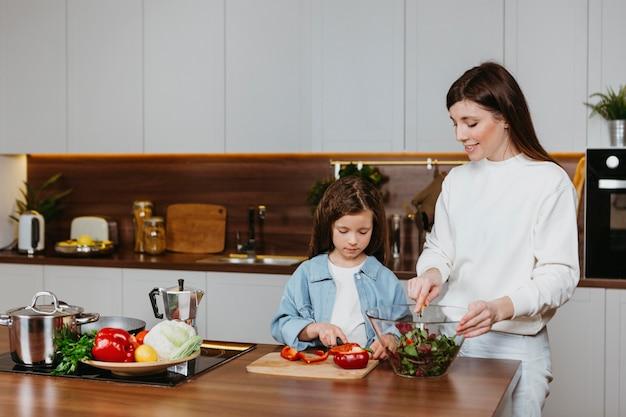 キッチンで食事を準備する母と娘の正面図 無料写真
