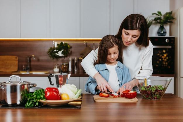 Вид спереди матери и девочки, готовящей еду на кухне Бесплатные Фотографии