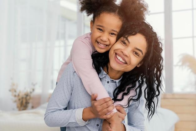 娘と家で遊んでいる母親の正面図 無料写真