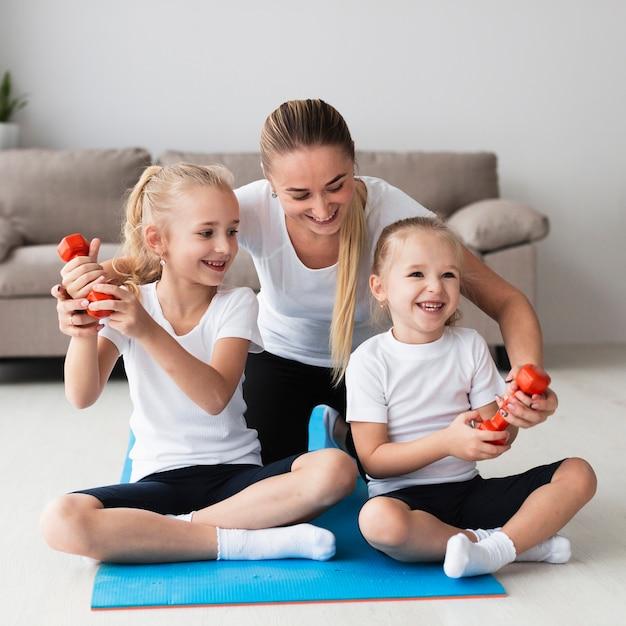 Вид спереди матери позирует с дочерьми дома, держа вес Бесплатные Фотографии