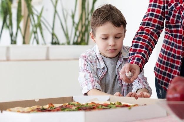 피자를 먹기 전에 아들의 손을 소독하는 어머니의 전면 모습 무료 사진