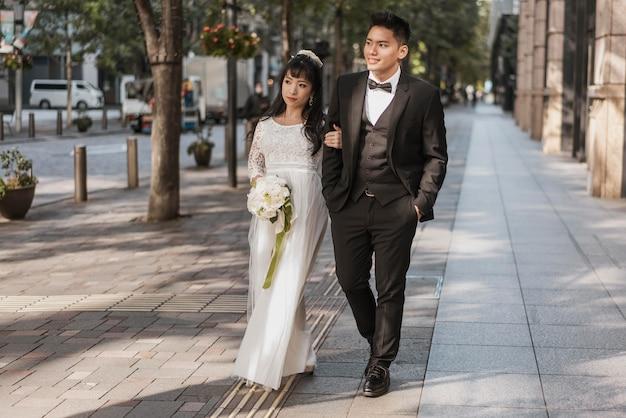 거리를 걷는 꽃의 부케와 함께 신혼 부부의 전면보기 프리미엄 사진