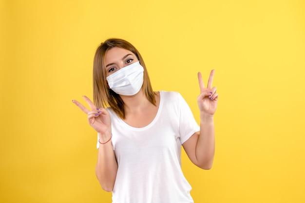 黄色の壁にマスクで若い女性の正面図 無料写真