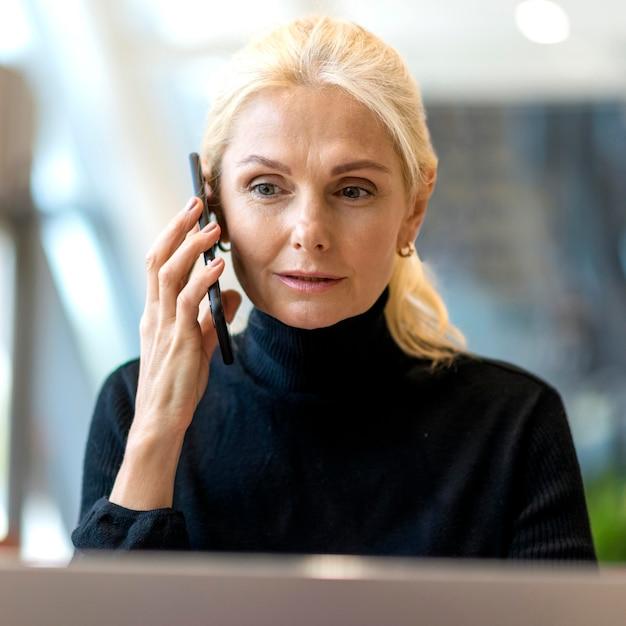 Вид спереди пожилой деловой женщины, говорящей на смартфоне Бесплатные Фотографии