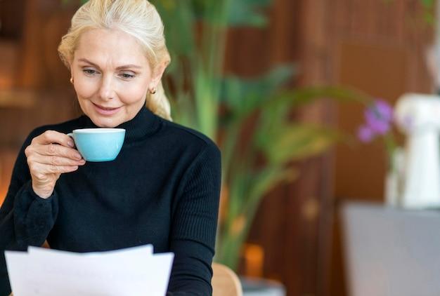 Вид спереди пожилой женщины на работе, читающей документы за чашкой кофе Бесплатные Фотографии